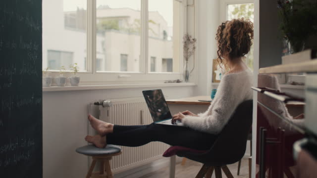 young woman typing on laptop at home in berlin - hemmakontor bildbanksvideor och videomaterial från bakom kulisserna