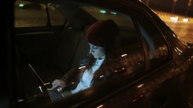 Young woman typing on laptop computer in a car.