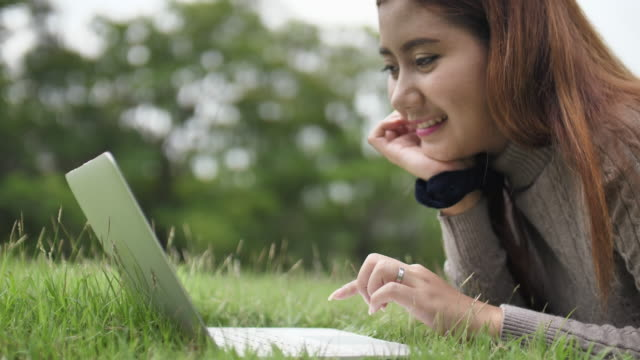 Young woman typing on laptop in the park