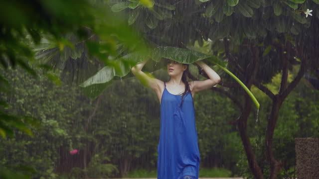 Young woman under a palm leaf in rain season, Delhi, India