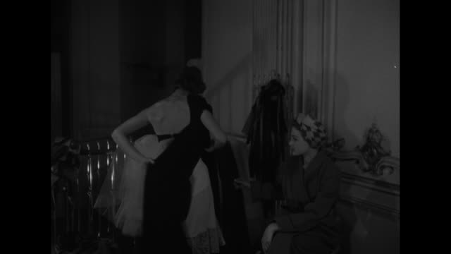MS young woman unfolds fabric of seamless dress as another woman looks on / MS young woman drapes the fabric on herself / CU woman's back as she...