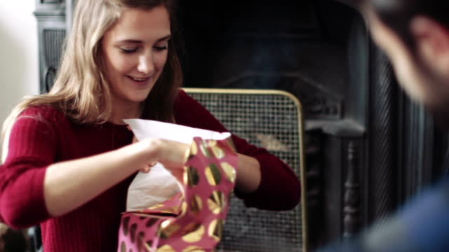 young woman unwrapping christmas gift - giving stock videos and b-roll footage