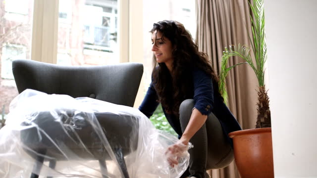 young woman unwrapping new chair - furniture stock videos & royalty-free footage
