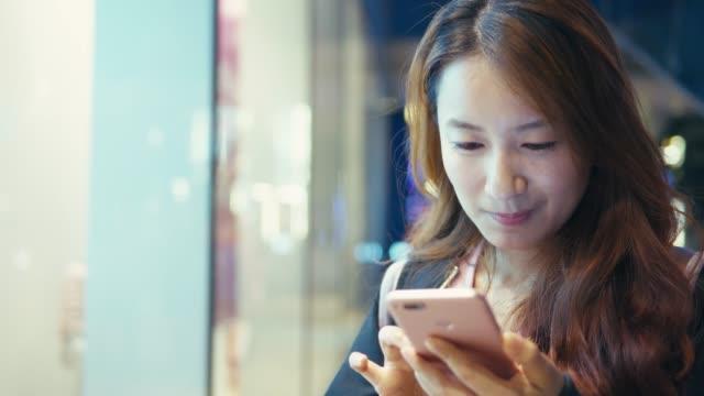 vídeos y material grabado en eventos de stock de joven mujer de uso del teléfono móvil en el centro comercial - miembro humano
