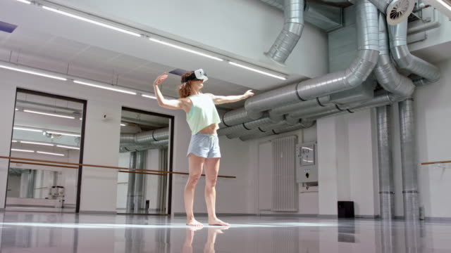 young woman uses a VR headset (virtual reality) while dancing in a studio