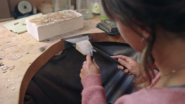 stockvideo's en b-roll-footage met young woman uses flat hand jewelry file to craft metal in workshop. - metaalindustrie