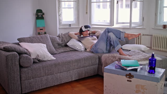 young woman uses her vr headset while lying on the couch - lying on back stock videos & royalty-free footage
