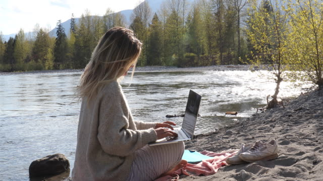 young woman uses laptop computer on river beach - serene people stock-videos und b-roll-filmmaterial