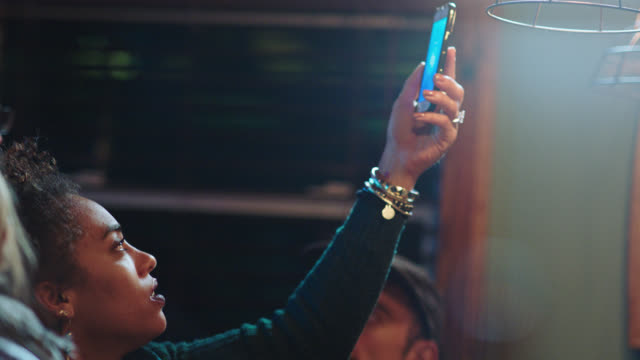young woman uses mobile app on smartphone to find song playing in local bar. - cercare video stock e b–roll