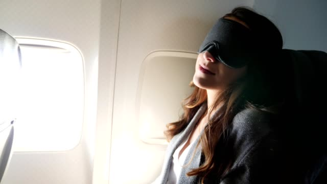 Jonge vrouw gebruikt slaapmasker tijdens een lange vlucht