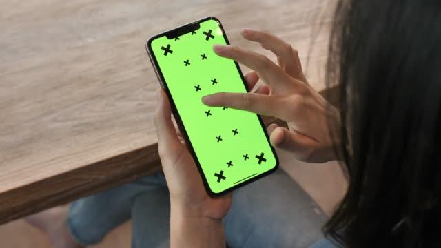 ung kvinna använder smart telefon med grön skärm - över axel perspektiv bildbanksvideor och videomaterial från bakom kulisserna