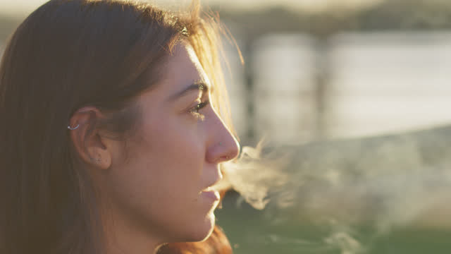 cu young woman uses smartphone and vapes outdoors - profile stock videos & royalty-free footage