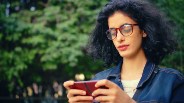 young woman uses smartphone at day time in park. - indian subcontinent ethnicity stock videos and b-roll footage