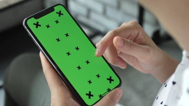 vídeos de stock, filmes e b-roll de jovem mulher usa smartphone com tela verde - send