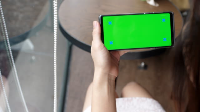 若い女性は、緑色の画面でスマート フォンを使用してください。 - 横位置点の映像素材/bロール