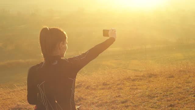 vídeos y material grabado en eventos de stock de joven mujer utiliza el teléfono inteligente para capturar la hermosa vista. - ropa de deporte