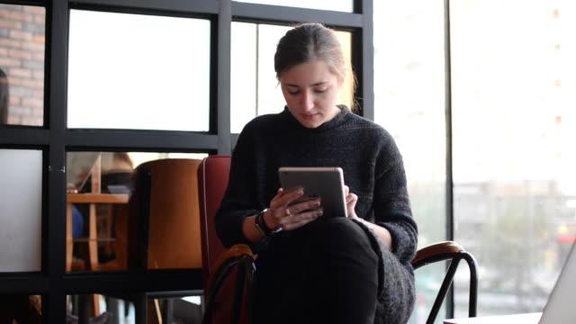 vídeos de stock, filmes e b-roll de young woman using a digital device at a coffee shop - vanguardista