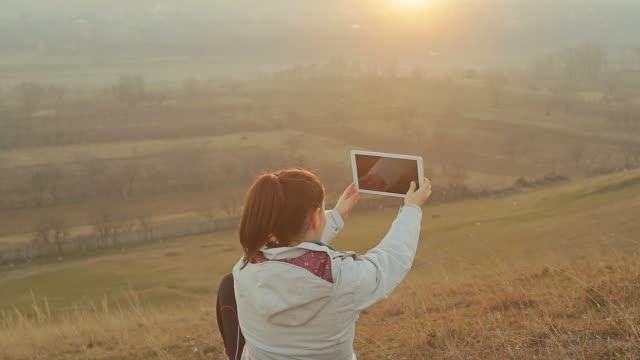 stockvideo's en b-roll-footage met jonge vrouw met behulp van een digitaal tablet in de natuur. - minder dan 10 seconden