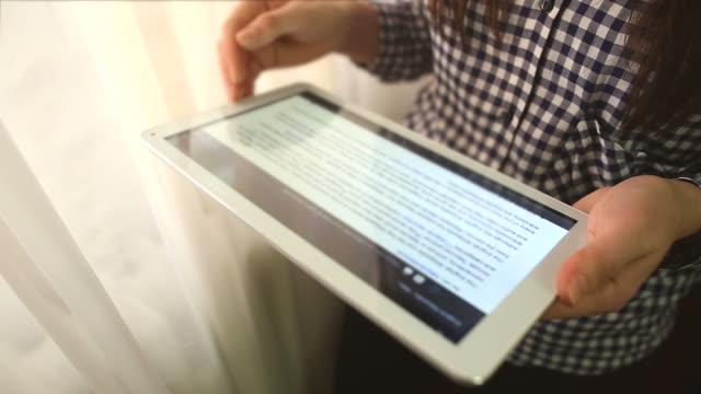 stockvideo's en b-roll-footage met jonge vrouw met behulp van een digitaal tablet. - artikel