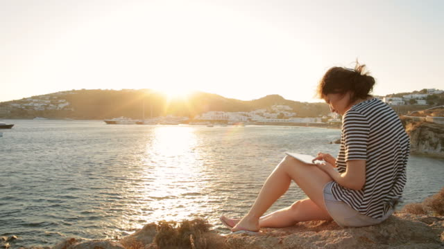 Young woman using a digital tablet while relaxing on the shore.