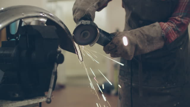 cu tu young woman using a grinder in a repair shop - metalwork stock videos & royalty-free footage