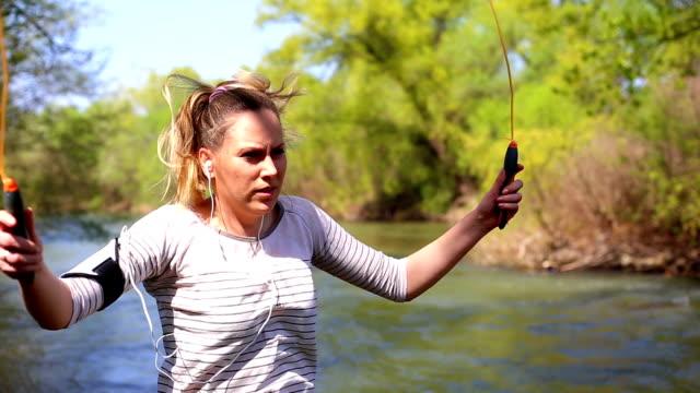Junge Frau mit einem Springseil in Park in der Nähe der Fluss
