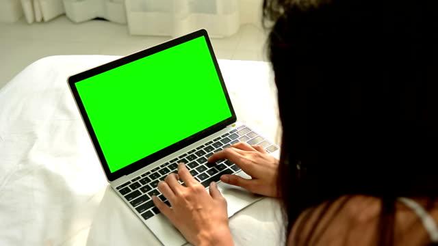 stockvideo's en b-roll-footage met jonge vrouw met behulp van een laptop computer met green screen monitor - keyable