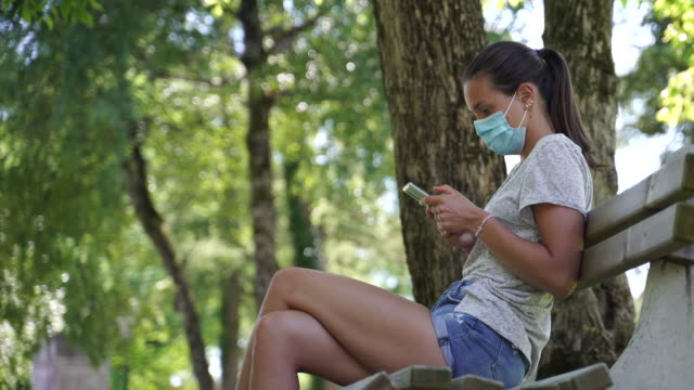 young woman using a mobil phone in a park while wearing a protective face mask - park bench stock videos & royalty-free footage