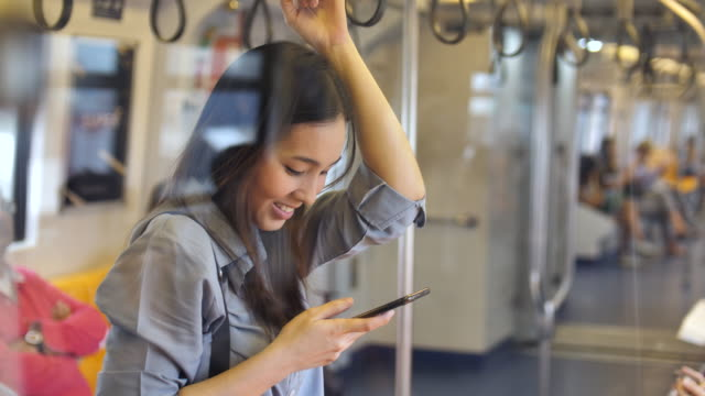 young woman using a smart phone on subway - ora di punta video stock e b–roll