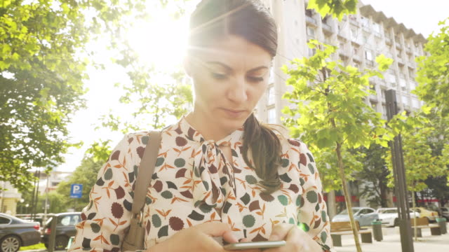 young woman using a smart phone. - pedestrian stock videos and b-roll footage