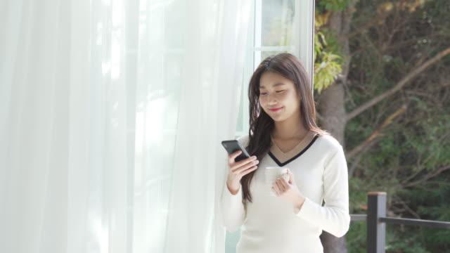 vídeos de stock e filmes b-roll de a young woman using a smartphone on the balcony - cara para baixo