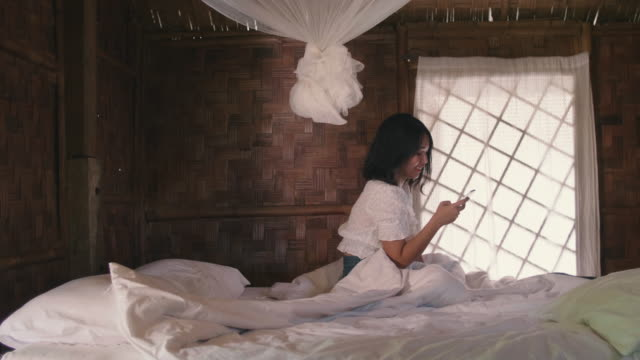 young woman using a smartphone while sitting in white bed in bedroom enjoying breeze in her hair. - netting stock videos & royalty-free footage