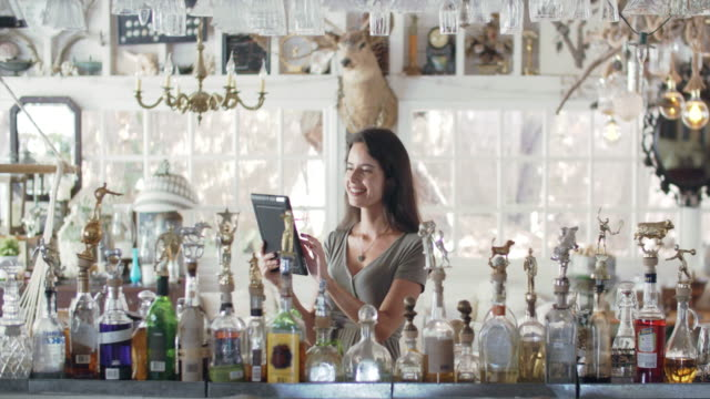vidéos et rushes de ws young woman using a tablet in a bar - directrice
