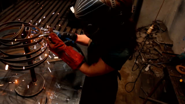 vídeos de stock e filmes b-roll de young woman using a welding machine - soldador