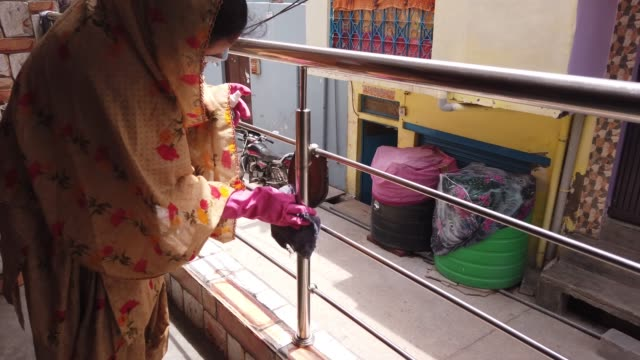 young woman using alcohol based sanitizer to wipe stainless steel railing of her house to disinfect because of corona pandemic - gartenhandschuh stock-videos und b-roll-filmmaterial