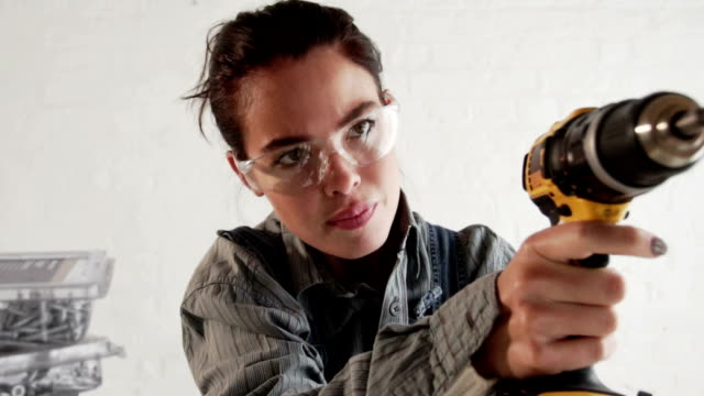 stockvideo's en b-roll-footage met young woman using an electric drill for diy  pr - doe het zelven