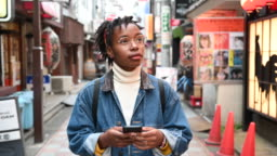 Young woman using app exploring streets of Tokyo