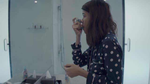 vidéos et rushes de jeune femme à l'aide d'inhalateur asthme dans les toilettes à la maison - inhalateur