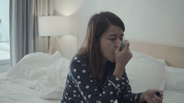young woman using asthma inhaler on the bed at home - inhaling stock videos & royalty-free footage