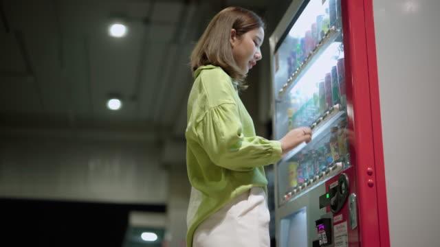 vidéos et rushes de jeune femme utilisant la machine d'eau automatique - machinerie