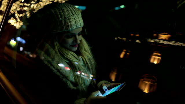 Young woman using cellphone while traveling in the car