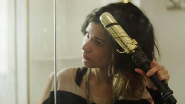 cu pan young woman using curling iron in front of bathroom mirror / provo, utah, usa - spole bildbanksvideor och videomaterial från bakom kulisserna