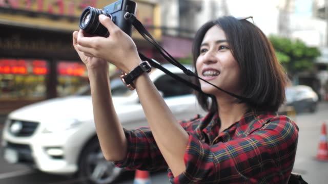 vidéos et rushes de jeune femme utilisant l'appareil-photo numérique - viser