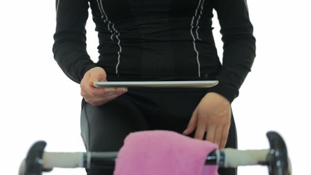 Junge Frau mit Digitaltablett und Übungen mit dem Fahrrad.