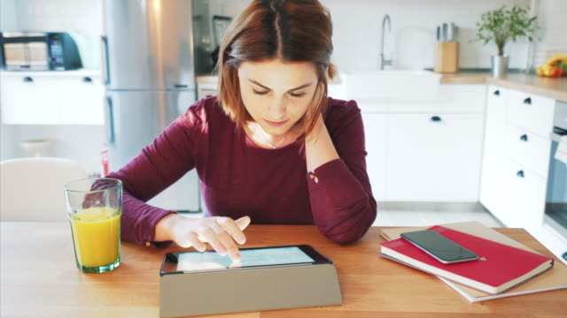 Young woman using digital tablet at home.