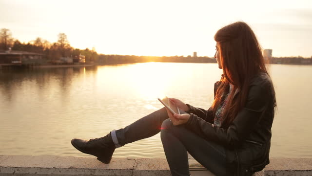 Young woman using digital tablet by the lake.