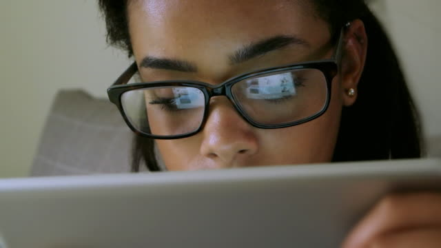 Young woman using digital tablet, glasses reflections.
