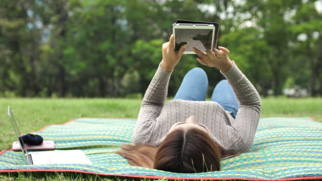 young woman using digital tablet in park - electronic book stock videos & royalty-free footage