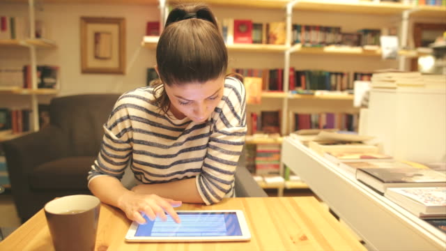 Young woman using digital tablet in the bookstore.