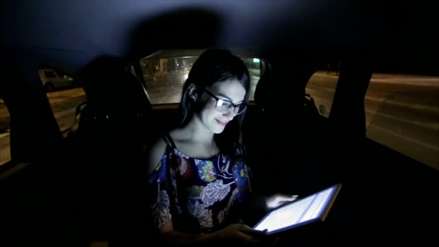 Young woman using digital tablet in the car at night